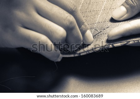 Closeup woman's hand sewing quilt in monotone color - stock photo