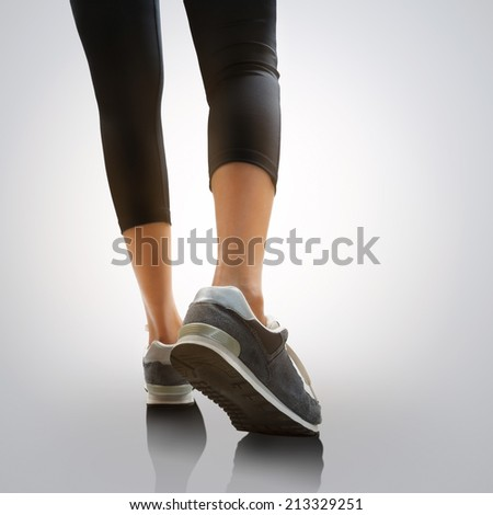 Closeup woman's legs walking, Isolated on grey background - stock photo