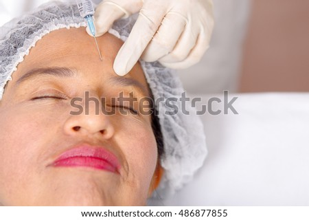 Closeup womans face receiving botox injections with syringe, cosmetic surgery concept, as seen from above