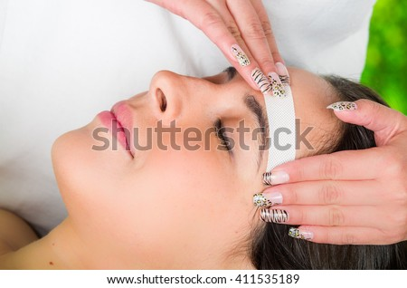 Closeup womans face receiving facial hair wax treatment, beauty and fashion concept