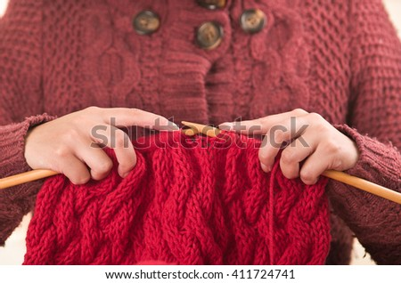 Closeup womans hands holding wooden knitting needles working on red scarf - stock photo