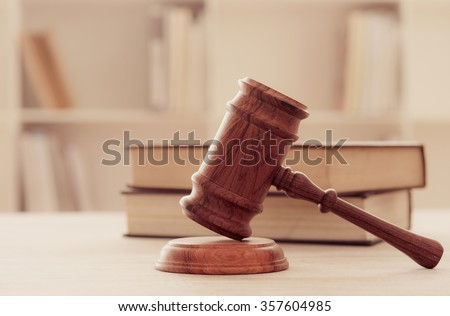 Closeup wooden judges gavel on wooden table with legal books. retro style. soft focus. concept of lawyers ruling. - stock photo