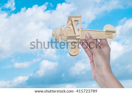 Closeup wooden plane in woman hand with blue sky in cloudy day background - stock photo