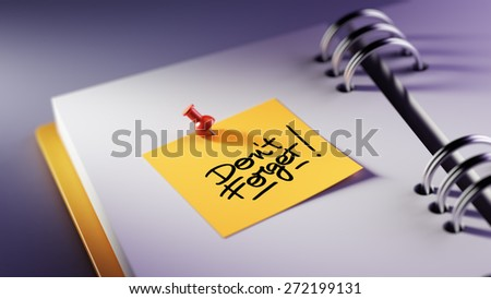 Closeup Yellow Sticky Note paste it in a notebook setting an appointment. The words Don`t Forget written on a white notebook to remind you an important appointment. - stock photo