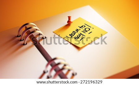 Closeup Yellow Sticky Note paste it in a notebook setting an appointment. The words Learn to say no written on a white notebook to remind you an important appointment. - stock photo