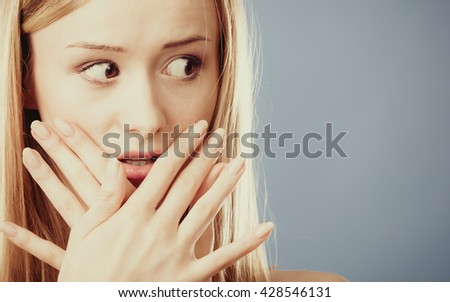 Closeup young amazed woman wide eyed covering her mouth with hands on  blue