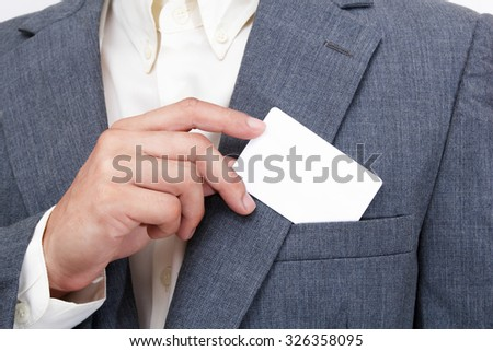 closeup young asian corporate guy hand showing white blank debit card in grey suit & white shirt - stock photo