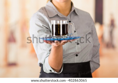 Closeup young brunette waitress wearing uniform, holding up tray containing two glasses of dark liquid using both hands - stock photo