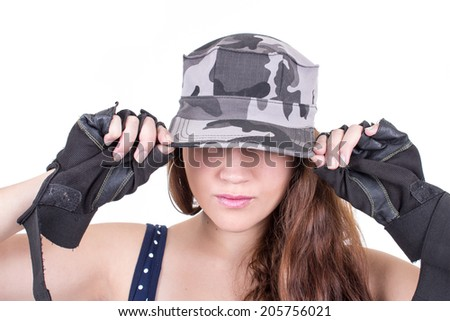 closeup young girl putting military cap on isolated over white - stock photo