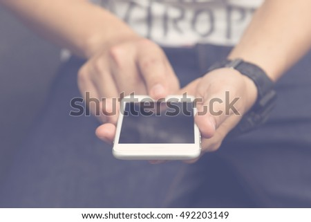 Closeup young smart man using smartphone outdoors, hands holding mobile smartphone, selective soft focus