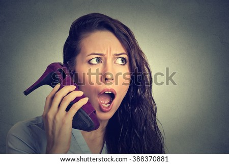 Closeup young woman looking excited, surprised holding high heeled shoe in her hand as  phone isolated on gray wall background. Human face expression. Funny girl with a shoe   - stock photo