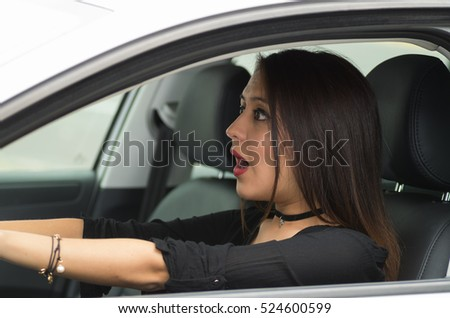 Closeup young woman sitting in car driving with interacting surprised, as seen from outside drivers window, female driver concept
