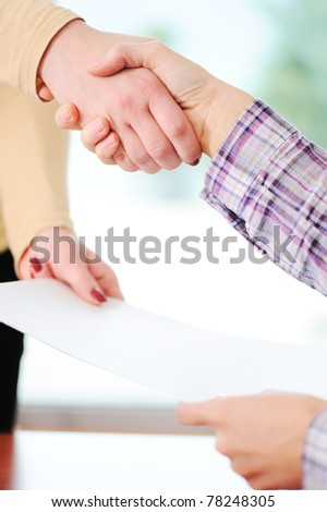 Closing a deal with a handshake. Signed contract in the hand between women. - stock photo