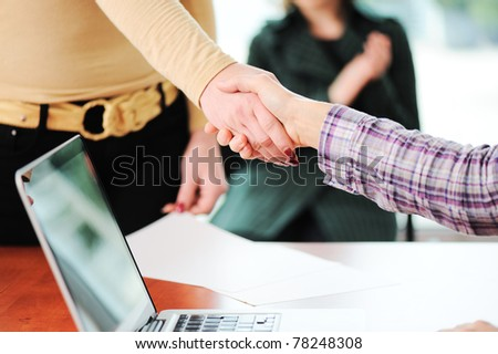 Closing a successful deal with a handshake. Signed contract and applause in the background. - stock photo