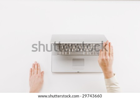 Closing Time - Hand shutting laptop computer on white background - stock photo