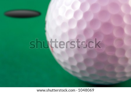 Closup of the dimples of a golf ball with hole in the background (shallow dof) - stock photo