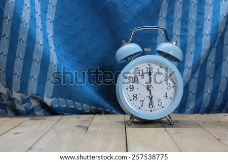 Cloth background with retro alarm clock on table