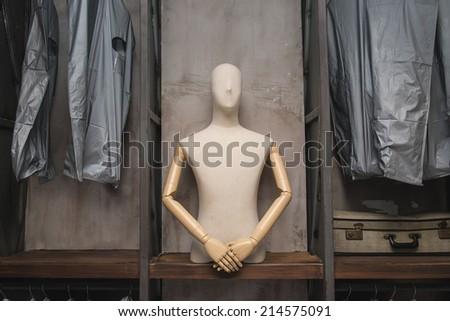 cloth dummy and bags in welcome polite manner on shelf - stock photo
