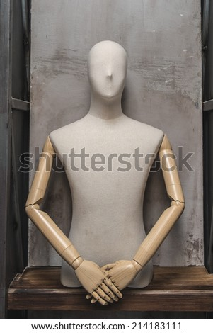 cloth dummy in welcome polite manner on shelf  - stock photo