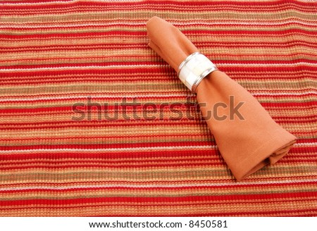 Cloth napkin with decorative napkin ring on striped placemat - stock photo