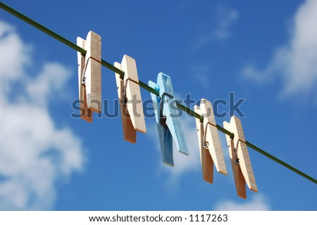 cloth pegs with a under the sky . A blue peg distinct from the other. - stock photo