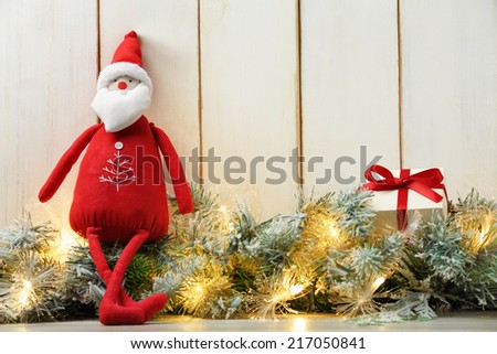 Cloth Santa Claus doll,Christmas lights and gift box on wood background. - stock photo