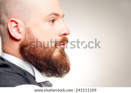 Clothed in confidence. Profile of young bearded man standing against grey background - stock photo
