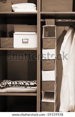 Clothes and towels in a wooden wardrobe - stock photo