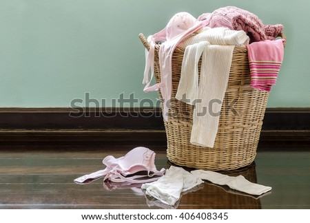 Clothes and underwear in rattan basket on the floor. - stock photo