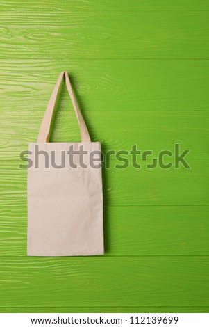 clothes bag on green background concept for save nature reused bag - stock photo