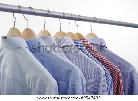 clothes hanger with shirts isolated on white background - stock photo