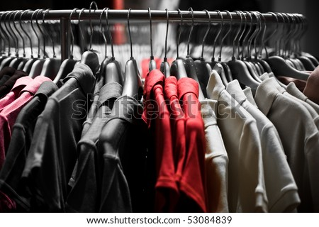 Clothes hangers with red t-shirts in store ready to choose to buy. Fashion shopping concept - stock photo