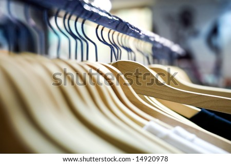 Clothes hangers with shirts in a store ready to sell. Fashion shopping store concept - stock photo