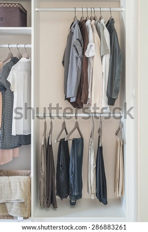 clothes hanging in white wardrobe at home - stock photo