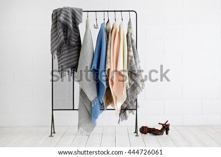 Clothes hanging on hanger isolated with white background and woman high heels on the ground. - stock photo