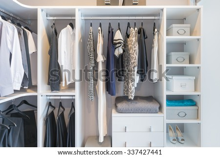 clothes hanging on rail in white wardrobe with box and shoes - stock photo