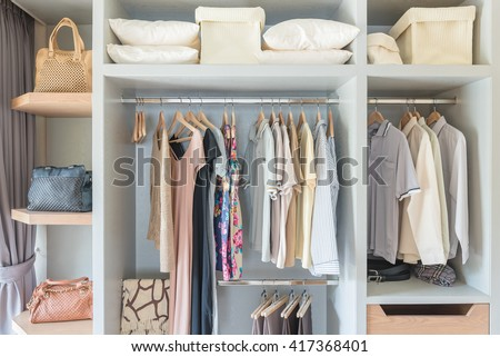 clothes hanging on rail in wooden closet at home - stock photo