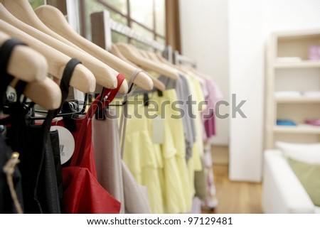 Clothes hanging on wooden hangers in a fashion store. - stock photo
