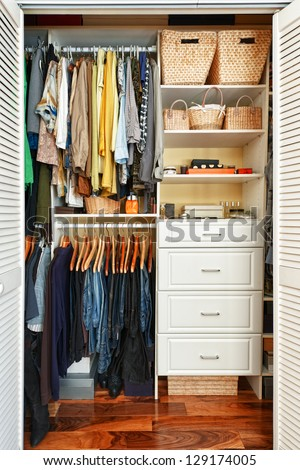 Clothes hung neatly in organized closet at home - stock photo