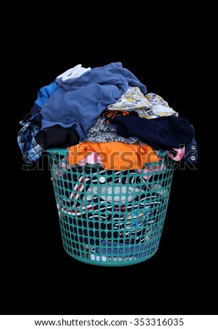 Clothes in a laundry basket isolated on black background - stock photo