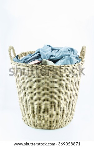 Clothes in a laundry wooden basket isolated on white background. - stock photo