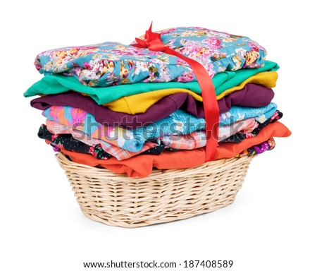 clothes in a wooden basket on isolated white background - stock photo