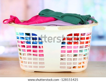 Clothes in plastic basket on table in room - stock photo