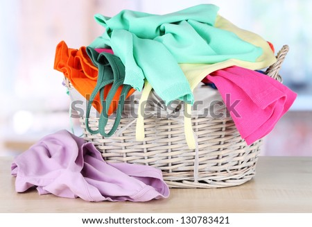 Clothes in wooden basket on table in room - stock photo