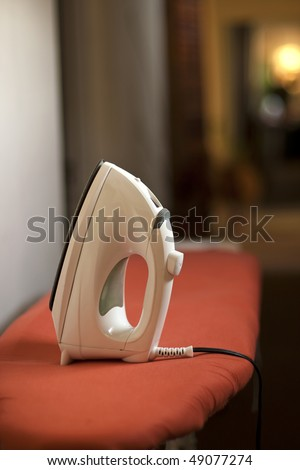 Clothes iron on ironing board - stock photo