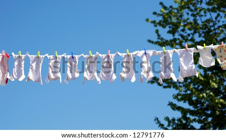 Clothes line full of reusable baby diapers in front of a clear blue sky