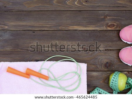 Clothes, objects, accessories for the sport. Running shoes,jump rope, a towel, an Apple, measuring tape and water bottle. The equipment on wooden background.Healthy eating. The place to advertise.