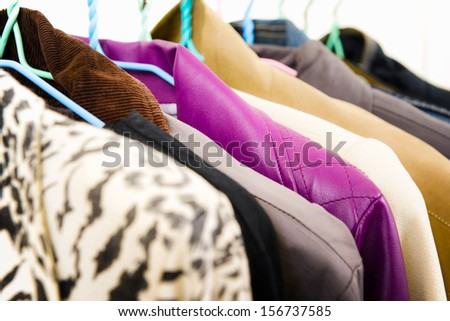 Clothes of different colors on hanger - stock photo
