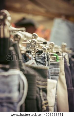 clothes on a rack on a flea market. - stock photo