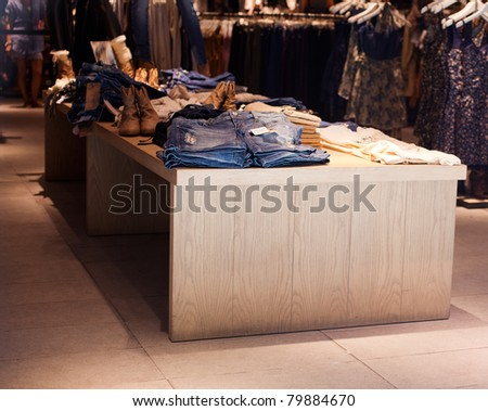 Clothes on a table in a Clothing store - stock photo